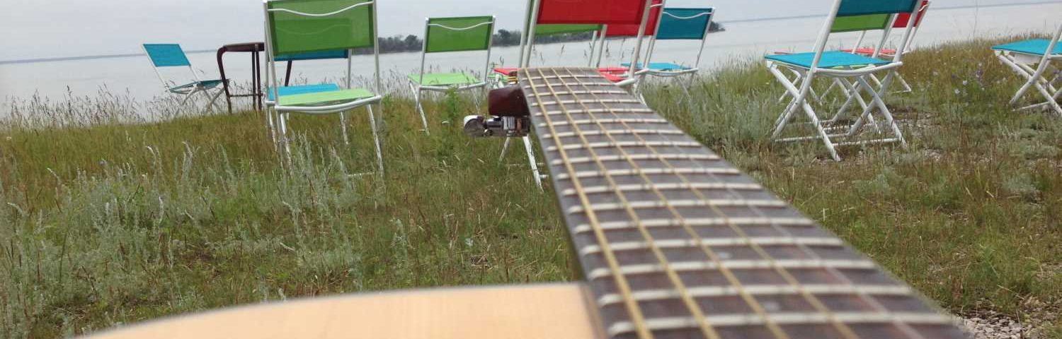Guitar with View of Chairs and Lake